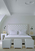 Double bed with white headboard and white cubic pouffes in bedroom
