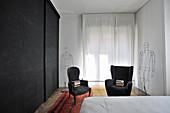 Schwarzer Kleiderschrank, schwarze Sessel und Draht-Skulpturen im Schlafzimmer