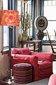 Red armchair, pouffe and standard lamp in front of console table and vintage scales