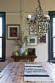 Rustic wooden dining table below wrought-iron chandelier