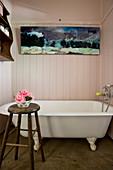 Vintage bathtub below painting in wood-clad bathroom with bowl of flowers on stool