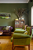 Green armchairs, half-height cabinet and vintage leather sofa in living room with green walls