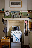Clock above gas cooker in disused fireplace