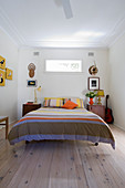 Double bed with striped bedspread and bedside cabinets in bedroom