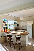 Breakfast bar in open-plan cream kitchen