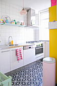 Black-and-white tiled floor in white kitchen with bright accents of bold colour