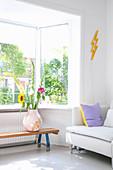 Blumenvase auf alter Gymnastikbank am Fenster