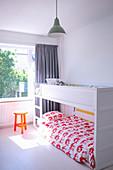 White bunk beds in light-flooded children's bedroom