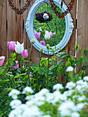 Vintage mirror and suspended rusty hearts behind bed of tulips