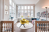 Yellow armchairs and blue sofa in living room with balustrade