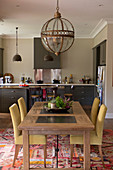 Dining table and upholstered chairs below pendant lamp with glass lampshade in open-plan kitchen
