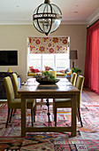 Dining table and upholstered chairs below pendant lamp with glass lampshade in open-plan interior