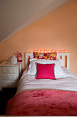 White bed and bedside cabinet in attic room with apricot wall