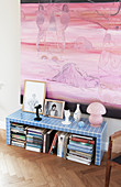 Books stacked below blue-tiled bench below pink painting