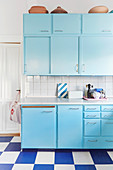 Pale blue retro kitchen with blue-and-white chequered floor