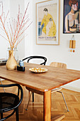 Simple wooden table and various chairs in front of art posters