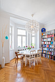 Oval table and chairs in front of bookshelves