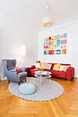Scatter cushions on red sofa, wing-back chair and coffee table in living room