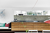Kitchen counter with pale wooden drawers in base units below narrow ribbon window