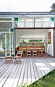 Wooden deck outside architect-designed house with large, open, glass sliding doors