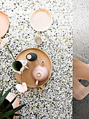 Top view of terrazzo table with tray, teapot and plates