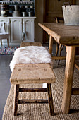 Fur rug on rustic wooden bench at dining table