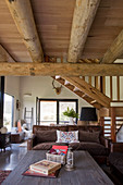 Rustic coffee table and couch in open-plan interior with wood-beamed ceiling