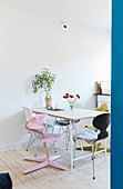 Ensemble of various designer chairs and high chair around dining table