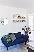 Contemporary blue sofa below shelves of crockery on wall in dining room