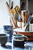 Ceramic cups, wooden plates and various cooking utensils in glass jars