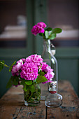 Posy of pink roses in glass of water on wooden table