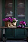 Pink roses in basket and metal vase