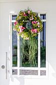 Door wreath with roses and grass on the front door