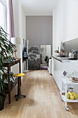 White kitchen counter opposite home workspace with wooden console table and swivel stool in narrow interior