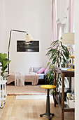 Sofa bed, standard lamp and wooden console table used as desk in foreground