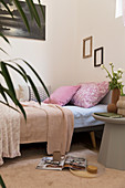 Pink pillows on sofa bed and grey side table in feminine apartment