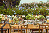 Table festively set with hydrangeas, roses and candle lanterns