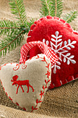 Small heart-shaped cushions decorated with moose and snowflake