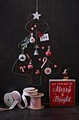 Stilisierter Weihnachtbaum aus Draht vor dunkler Wand