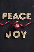 Weihnachtsdekoration aus Plätzchen, roter Kugel und Geschenkband