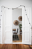 Fairy lights draped around open panelled doors in period apartment with view into festively decorated dining room