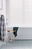 Free-standing bathtub below window with louvre blind in bathroom