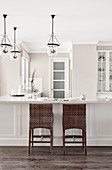 L-shaped kitchen counter with bar stools below pendant lamps