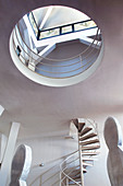 Spiral staircase and artwork in loft apartment with circular aperture below skylight