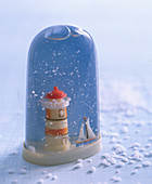 Tall snow globe containing lighthouse and sailing boat