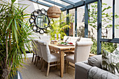 Upholstered chairs around wooden table in conservatory with tropical character