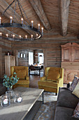 Chandelier and yellow armchairs in living room of log cabin