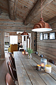 Copper-coloured lampshades above rustic dining table in log cabin