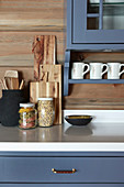 Storage jars and chopping boards in country-house kitchen with blue cupboards