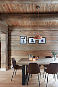 Modern upholstered chairs around dining table in modern log cabin